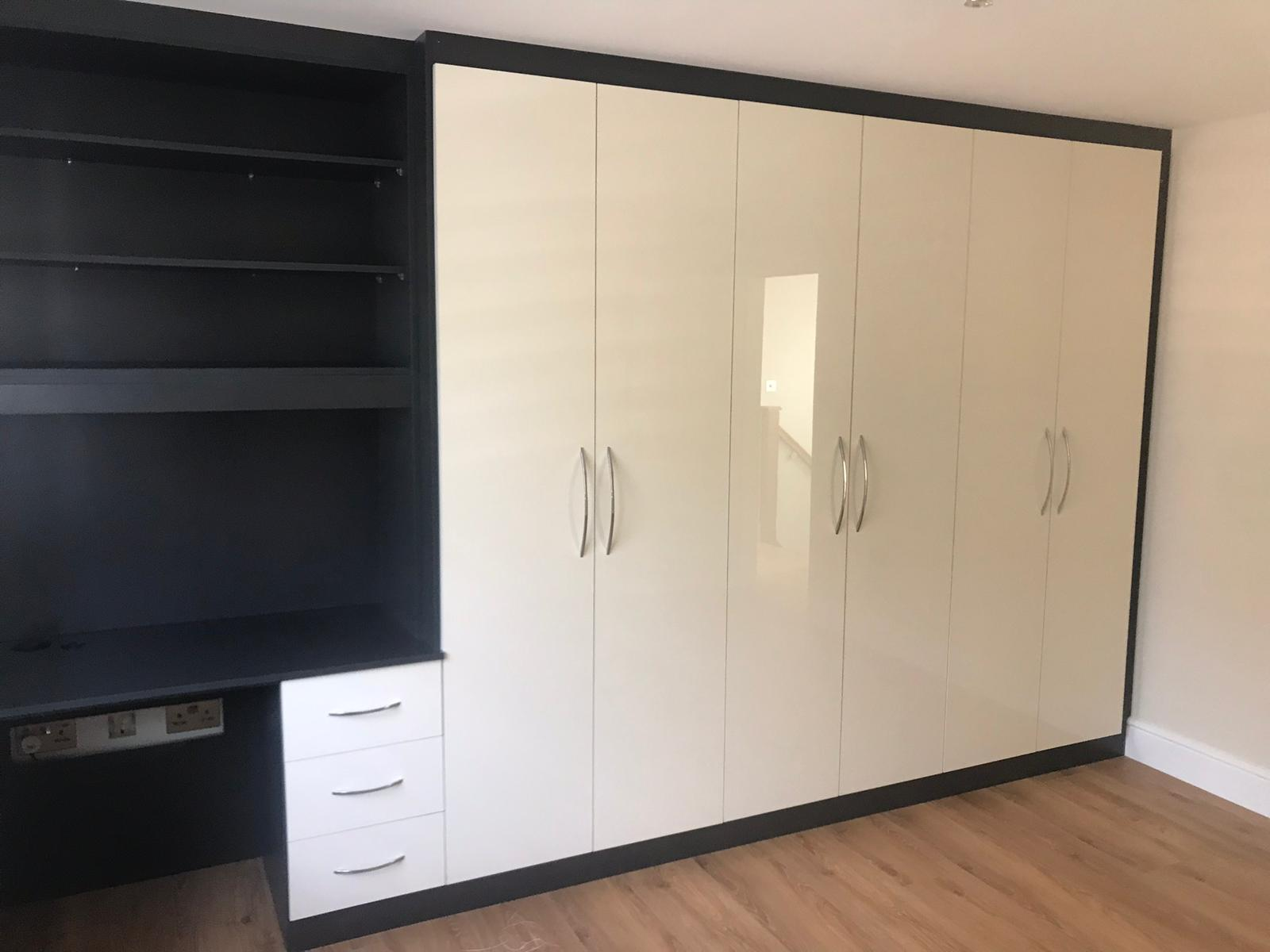 Bespoke fitted wardrobe utilizing a high gloss ultra-white and pebble black wood